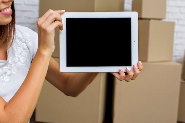 Gelukkige vrouw die een tabletmodel houdt
