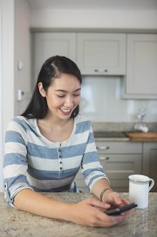 Gelukkige vrouw die een tekstbericht op haar mobiele telefoon in keuken typt