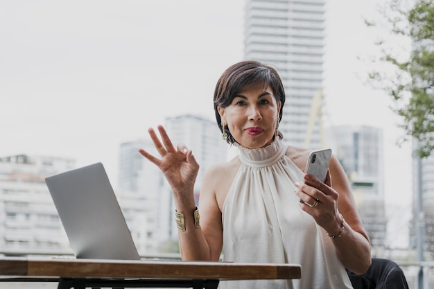 Gelukkige vrouw die een telefoon op stedelijke achtergrond houdt