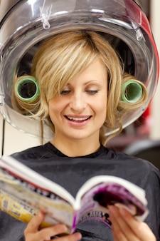 Gelukkige vrouw die een tijdschrift met haarkrulspelden leest onder een hairdryer