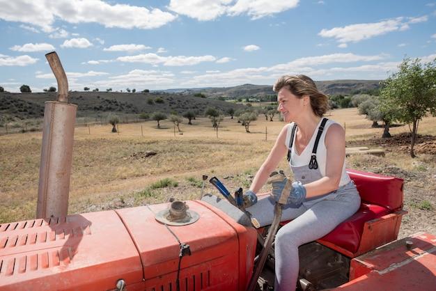 Gelukkige vrouw die een tractor op het gebied drijft