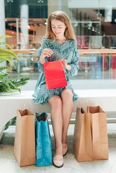 Gelukkige vrouw die één van haar zakken controleert
