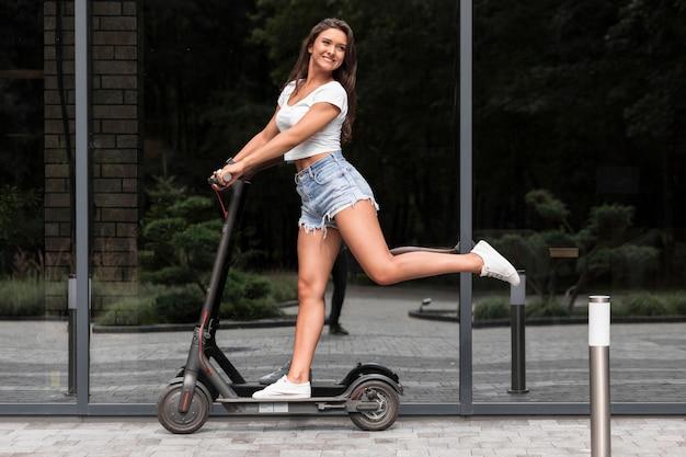 Gelukkige vrouw die elektrische autoped buiten berijdt