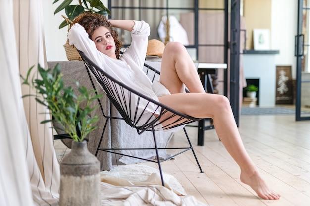 Gelukkige vrouw die en thuis van stress vrij weekend ontspannen genieten, kalm tevreden meisje het uitrekken bij laag het denken aan prettige luie dag