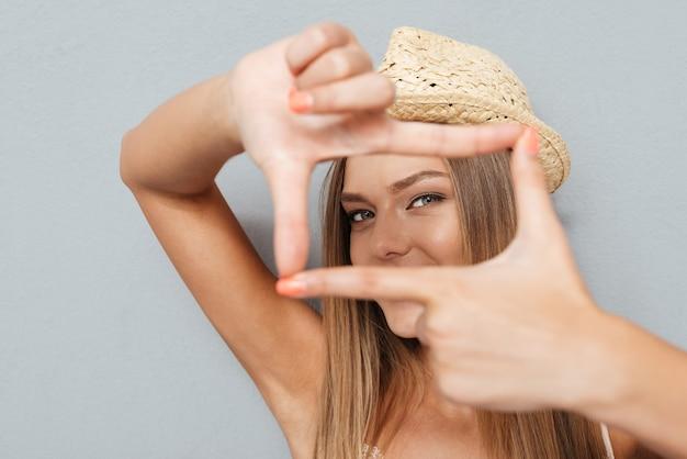 Gelukkige vrouw die frame met vingers maakt die op een grijze achtergrond worden geïsoleerd