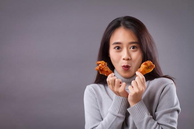 Gelukkige vrouw die gebraden kip eet