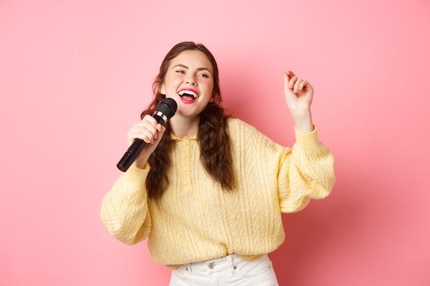 Gelukkige vrouw die geniet van het zingen van karaoke met microfoon en opzij kijkt, dansen en plezier maken over roze muur