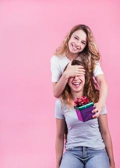 Gelukkige vrouw die giftdoos geeft aan haar zuster tegen roze achtergrond