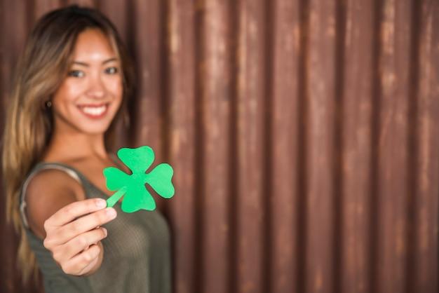 Gelukkige vrouw die groenboekklaver houdt