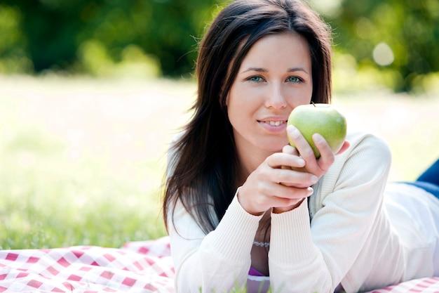 Gelukkige vrouw die groene appel houdt