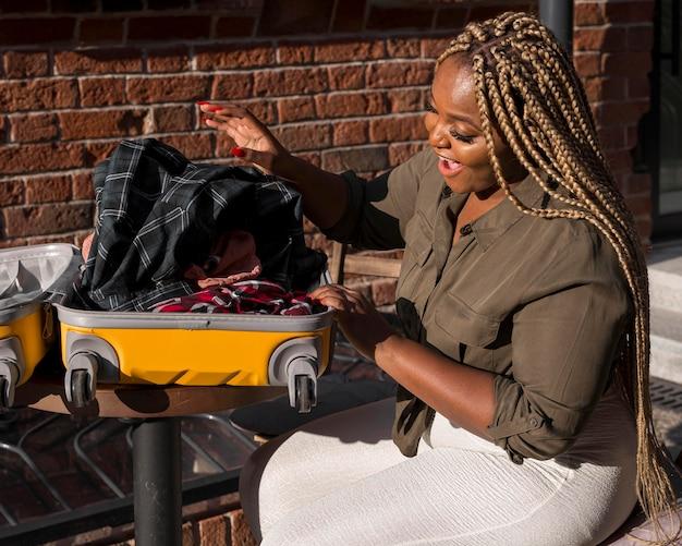 Gelukkige vrouw die haar geopende bagage bekijkt