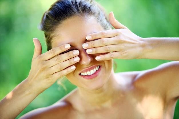 Gelukkige vrouw die haar gezicht behandelt met handen