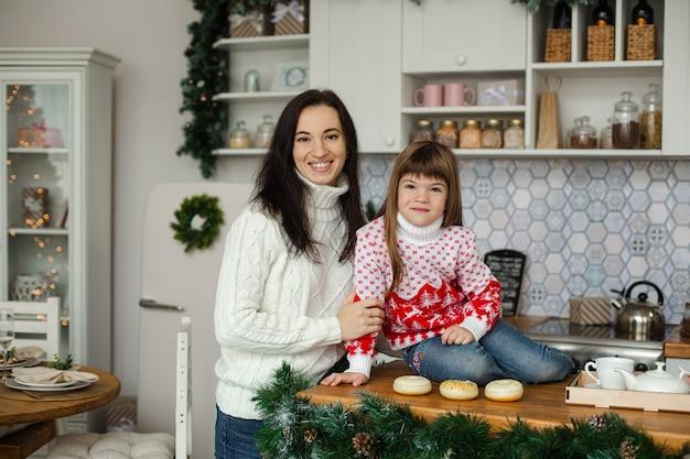 Gelukkige vrouw die haar kind koestert terwijl hij in de keuken staat