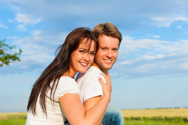 Gelukkige vrouw die haar man in de aard omhelst