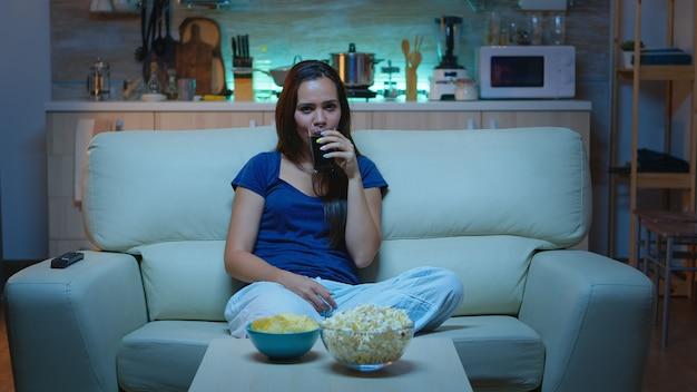Gelukkige vrouw die haar vrije tijd doorbrengt met tv-kijken, popcorn eten en sap drinken. opgewonden geamuseerde alleen thuis dame genieten van de avond thuis zittend op een comfortabele bank gekleed in pyjama.