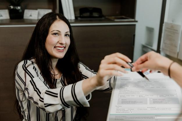 Gelukkige vrouw die het contract overhandigt aan de klant