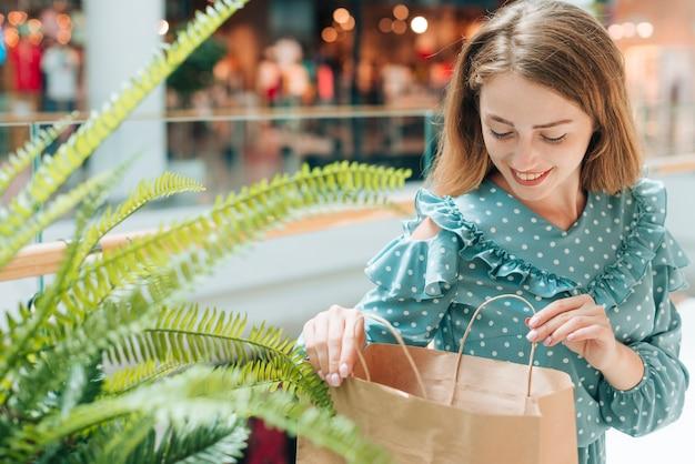 Gelukkige vrouw die het winkelen zakken controleert