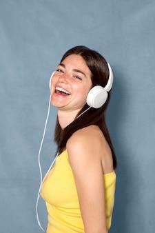 Gelukkige vrouw die hoofdtelefoons draagt