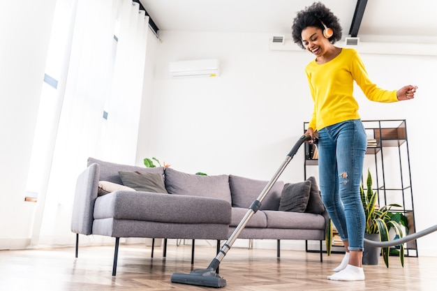 Gelukkige vrouw die huis schoonmaakt met stofzuiger en muziek luistert