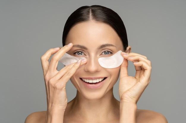 Gelukkige vrouw die hydrogel patches voor herstel onder de ogen toepast