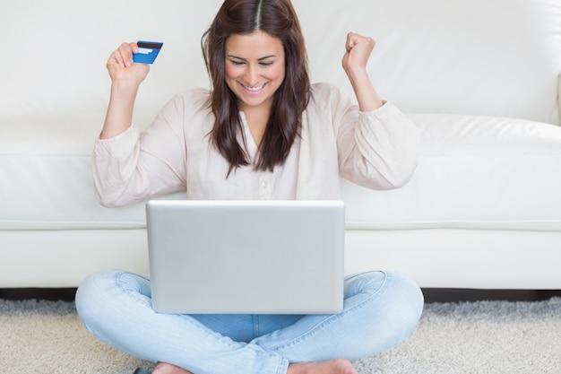 Gelukkige vrouw die iets online koopt
