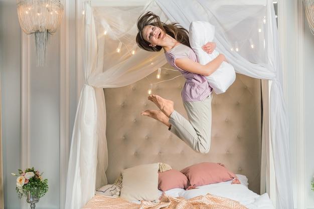 Gelukkige vrouw die in bed springt