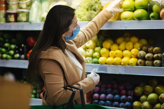 Gelukkige vrouw die in beschermend masker verse groenten neemt terwijl status door boodschappen in supermarkt