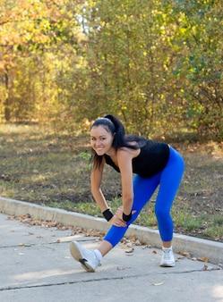 Gelukkige vrouw die in een park oefent die voorwaarts op haar gestrekte been buigt om haar spieren te strekken tijdens het opwarmen