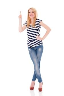 Gelukkige vrouw die in gestreepte blouse op copyspace richt