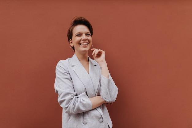 Gelukkige vrouw die in grijze jas op bruine achtergrond lacht. vrolijk jong meisje in oversized stijlvol pak glimlacht en poseert op geïsoleerd
