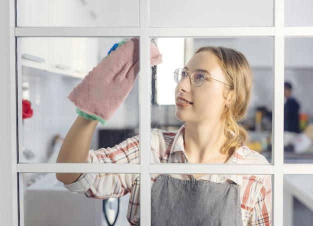 Gelukkige vrouw die in handschoenen het glasvenster bij huiskeuken schoonmaken. huishoudelijk werkconcept.