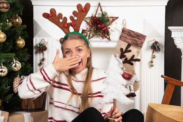 Gelukkige vrouw die in hertenoren witte kerstboom houdt en haar mond behandelt.