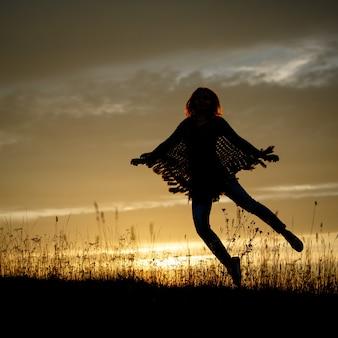 Gelukkige vrouw die in het veld springt bij zonsondergang