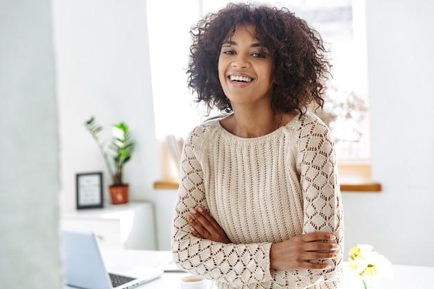 Gelukkige vrouw die in vrijetijdskleding naar de camera kijkt met gekruiste armen terwijl ze bij de tafel op kantoor staat