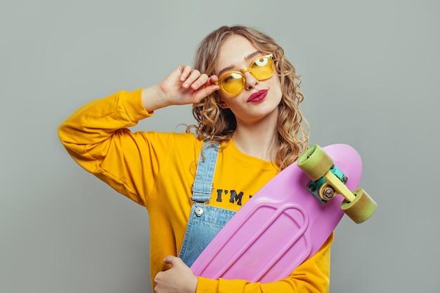 Gelukkige vrouw die in zonnebril roze skateboard houdt