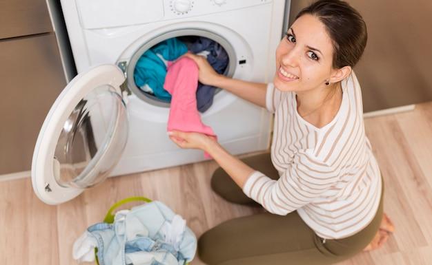 Gelukkige vrouw die kleren uit machine neemt