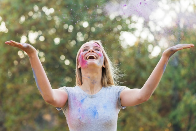 Gelukkige vrouw die kleur in de lucht werpt