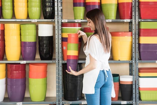 Gelukkige vrouw die kleurrijke bloeiende potten voor plank houdt