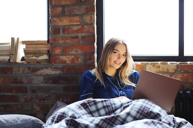 Gelukkige vrouw die laptop op bed met behulp van