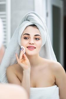 Gelukkige vrouw die make-up reinigingspads lotion badkamerspiegel in de badkamer verwijdert