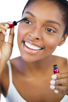 Gelukkige vrouw die mascara voor haar wimpers gebruikt