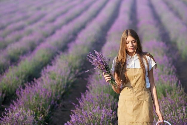 Gelukkige vrouw die met bloemen op lavendelgebied loopt