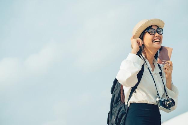 Gelukkige vrouw die met camera en paspoort op reis per vliegtuig wachten.