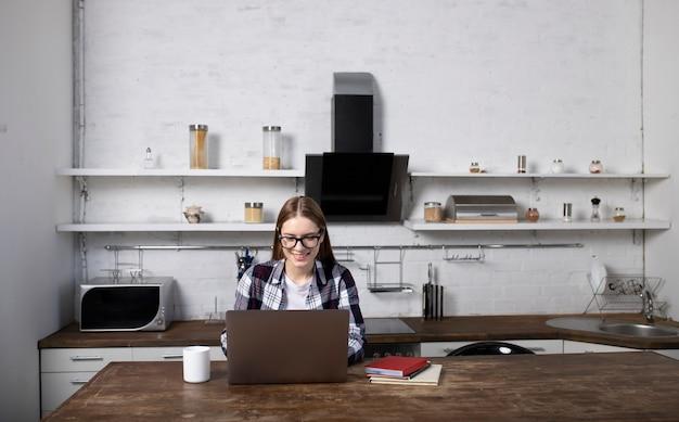 Gelukkige vrouw die met een bril 's ochtends thuis werkt. meisje dat koffie drinkt. ze gebruikt haar laptop