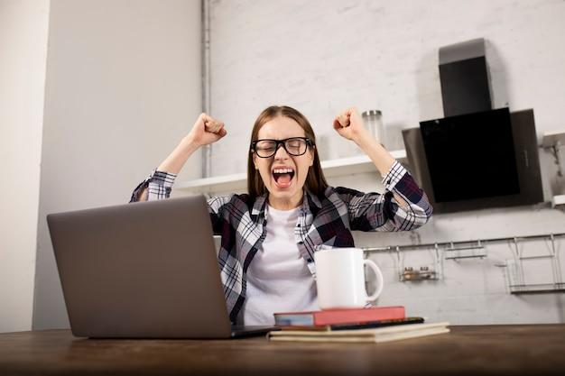 Gelukkige vrouw die met een bril 's ochtends thuis werkt. meisje drinkt koffie. ze gebruikt haar laptop