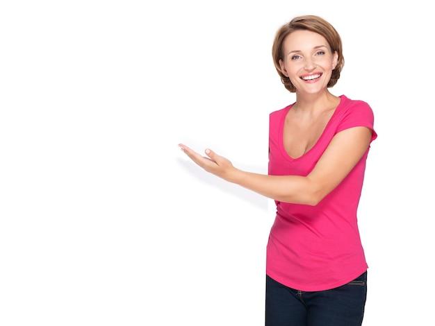 Gelukkige vrouw die met haar vinger op banner richt die op witte muur wordt geïsoleerd