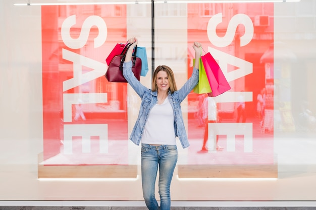 Gelukkige vrouw die met het winkelen zakken haar wapens opheft