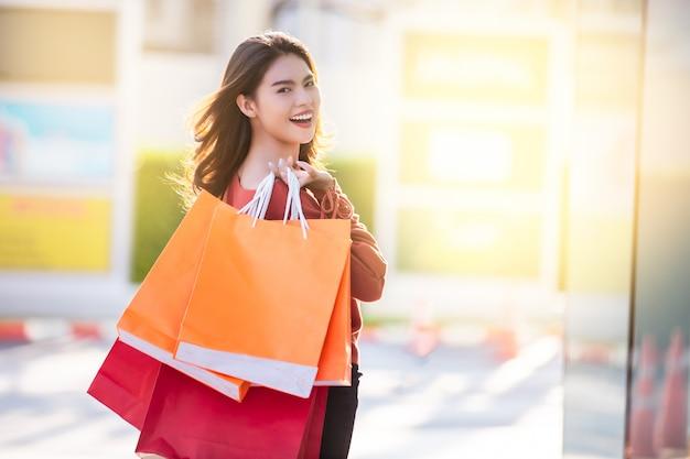 Gelukkige vrouw die met het winkelen zakken in het winkelen genieten van