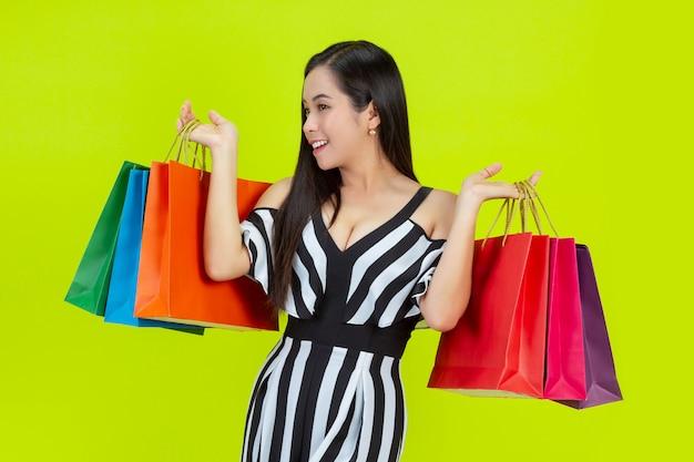 Gelukkige vrouw die met het winkelen zakken winkelt