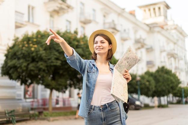 Gelukkige vrouw die met hoed op landschap richt